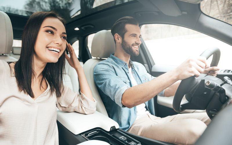 Junges Paar im PKW freut sich über Fahrzeug-Desinfektion